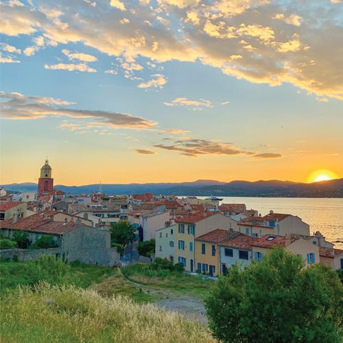 Photo prise en hauteur sur le village de Saint Tropez où il y a un couché de soleil sur les montagnes.