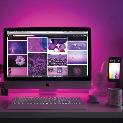 Ordinateur IMAC et téléphone Iphone montrant des photos de fleurs, de ballons et d'eau. Derrière les écrans, le mur reflète violet.
