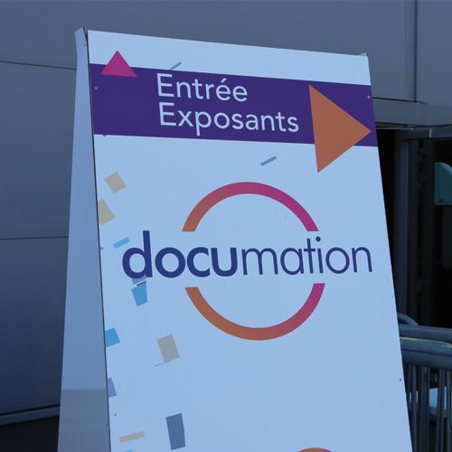 kakemono devant une porte présentant le Salon Documation. Il y a le logo du salon.